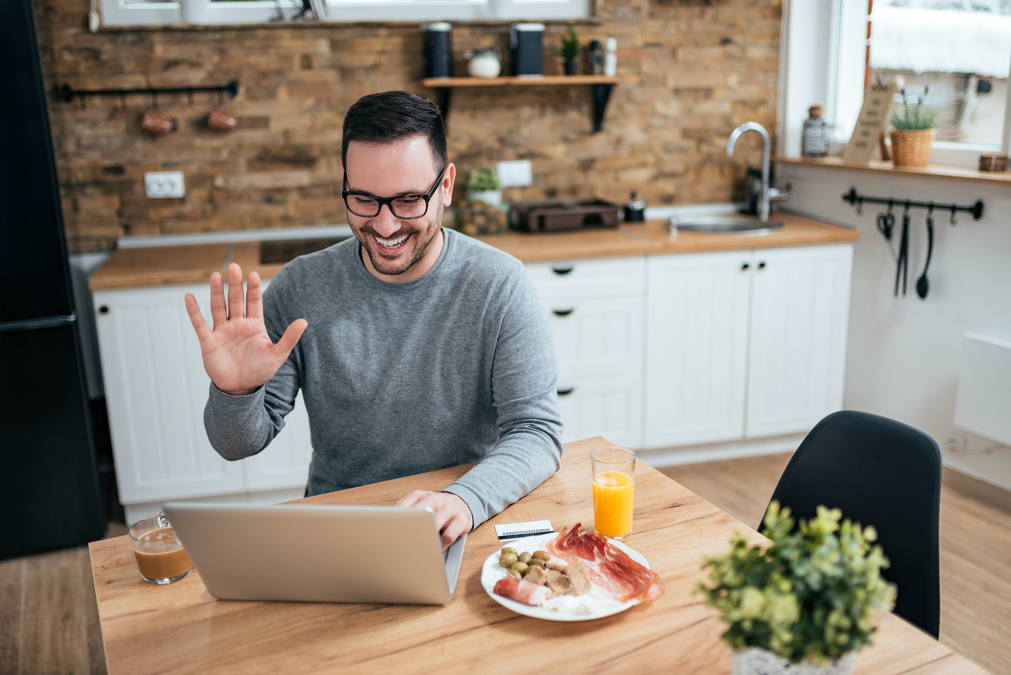 Smiling man enjoying breakfast in the kitchen and having a video call on laptop.